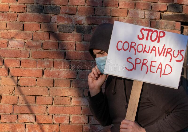 Man with banner Stop Spread. Man protests, calling governments to help fight corona virus. Person encourage scientists. To stop pandemic. Person with mask stock images