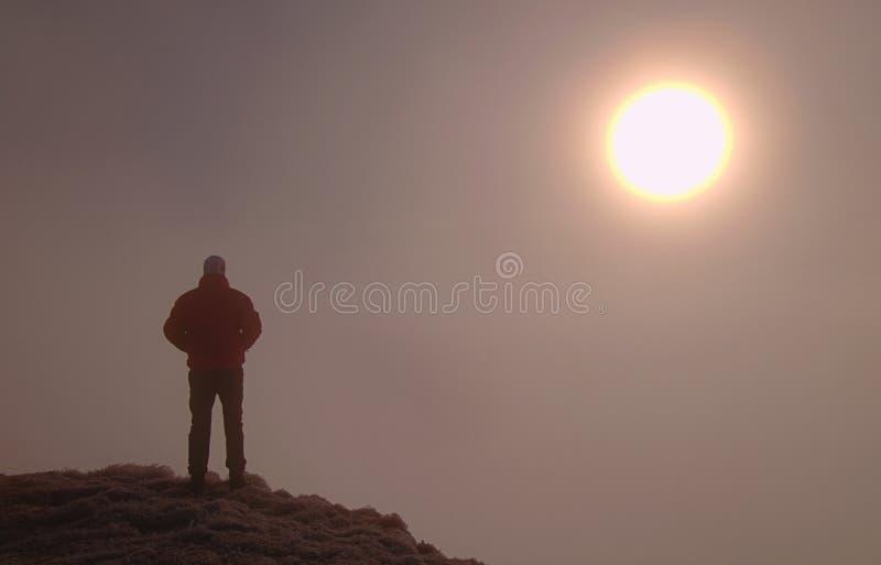 Man bara på toppmöte Mannen tycker om att stå ovanför den bullriga världen arkivbild