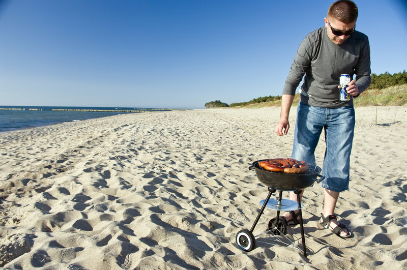 Man and barbecue on beach royalty free stock photography
