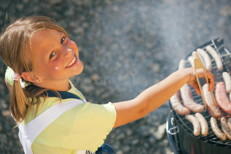 Man at the barbecue grill. Little girl preparing meat and sausages using a barbecue grill royalty free stock images