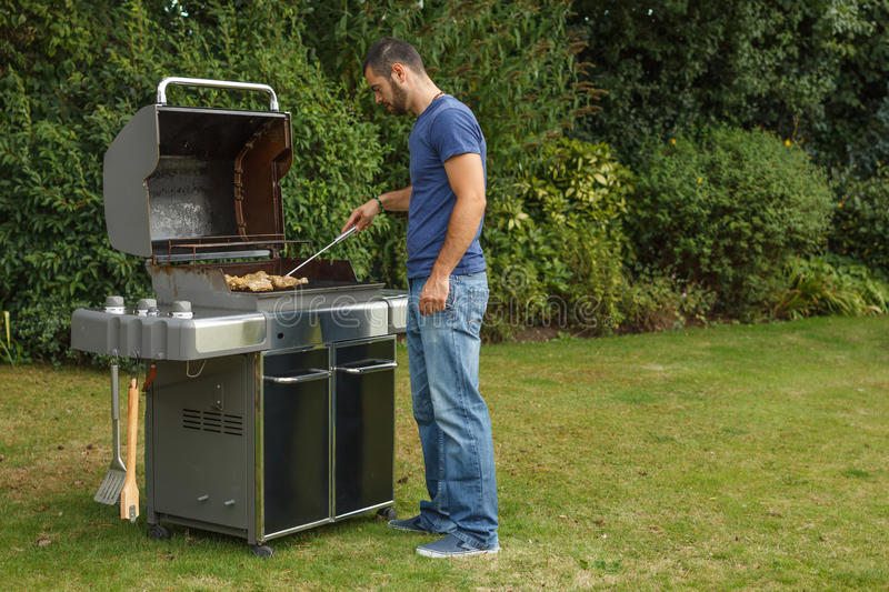 Man at a barbecue grill. Young man at a barbecue grill stock images