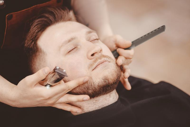 Man Barber shaves beard of client on chair Barbershop royalty free stock images