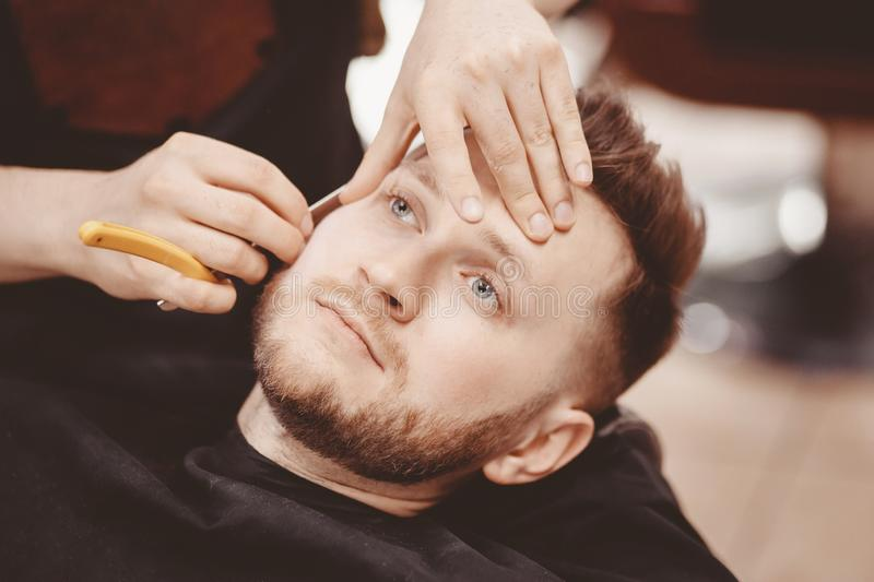 Man Barber shaves beard of client on chair Barbershop royalty free stock photography