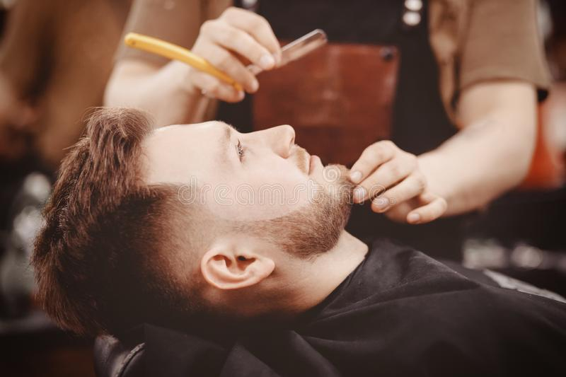 Man Barber shaves beard of client on chair Barbershop stock images