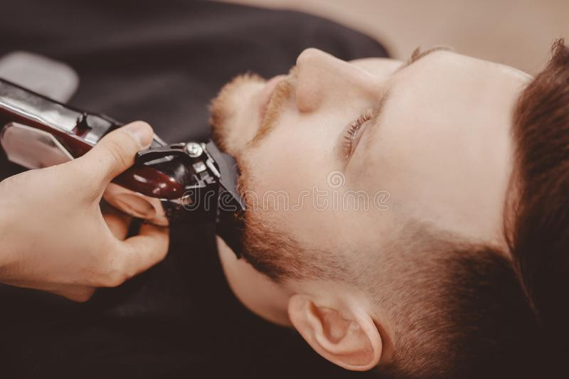 Man Barber shaves beard of client on chair Barbershop stock photography