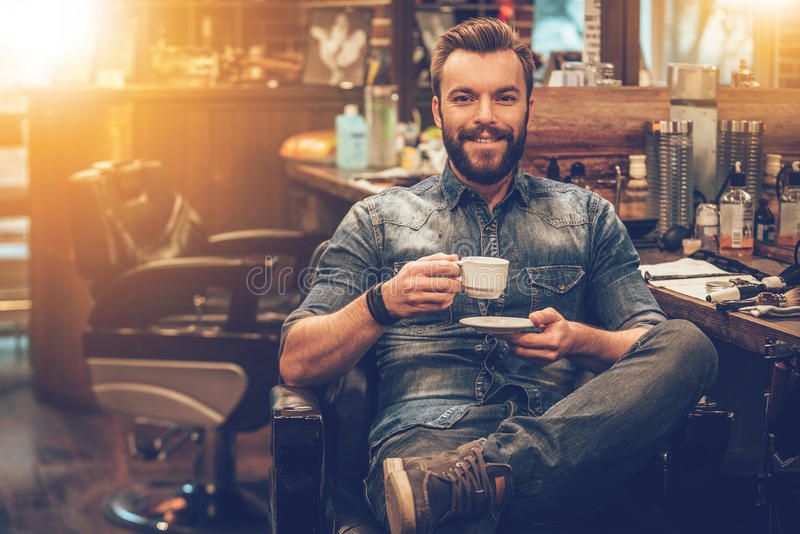 Man at barbershop. Cheerful young bearded man looking at camera and holding coffee cup while sitting in chair at barbershop royalty free stock photography