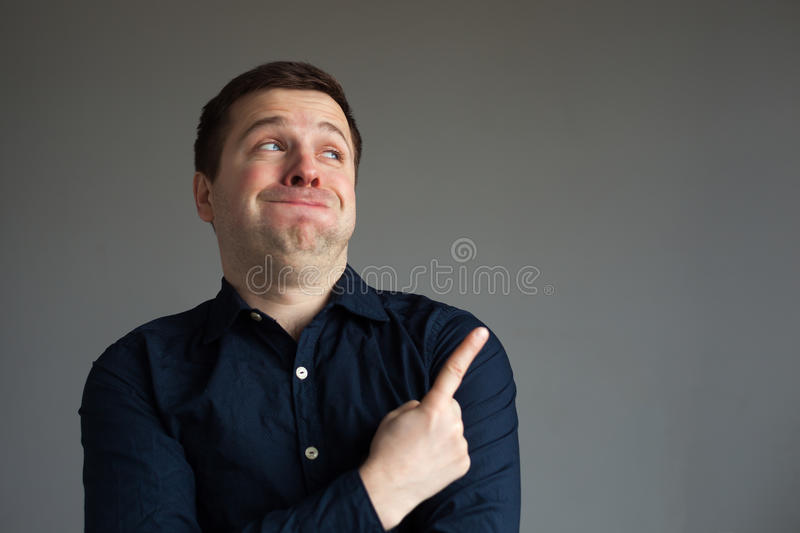 The man barely holds back from laughing. And points with his index finger at interesting information royalty free stock image