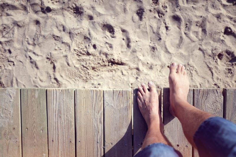 Man barfota att kliva av strandpromenad på strandsanden arkivbilder