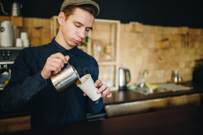 Man barista prepares delicious coffee near the wall construted is small desk squares stock photo