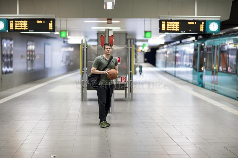 Man With a Basketball Standing at a Subway Station Platform. A man with a basketball and dressed in activewear standing at a subway station platform in Frankfurt stock photography