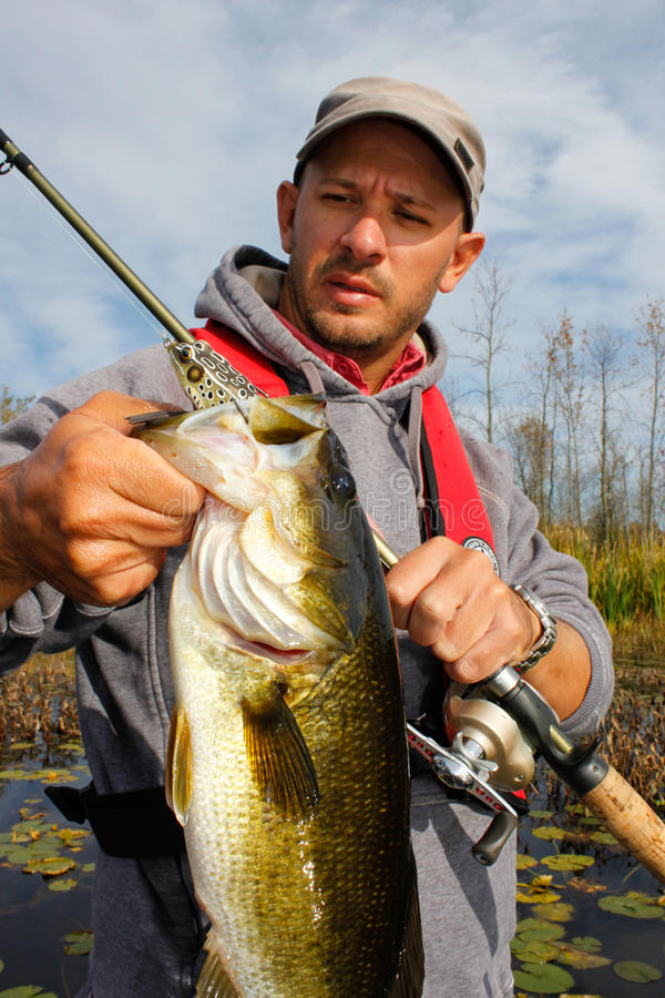 Man Fishing Large Mouth Bass. A man holds a largemouth bass he caught while fishing a topwater frog lure royalty free stock photography