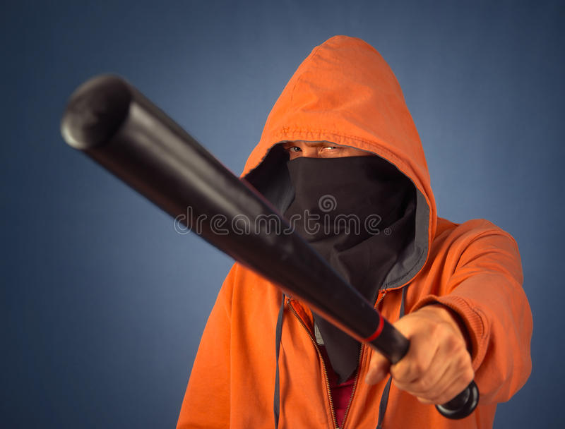 Man with bat. Bandit man in the mask threatens bat on a dark background royalty free stock image