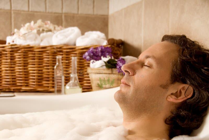 Man in bath. Man client in a spa taking an aroma bath