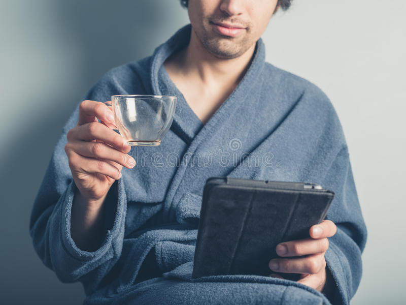 Man in bathrobe with empty cup using tablet royalty free stock photography