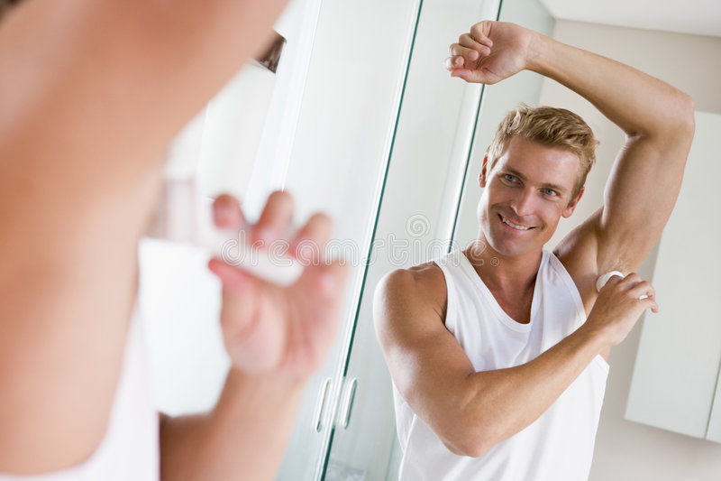 Man in bathroom applying deodorant royalty free stock image