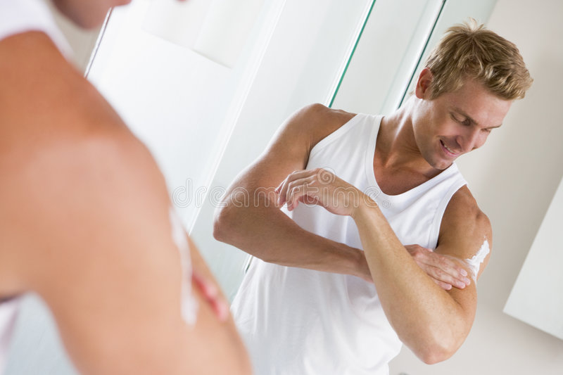 Man in bathroom applying lotion stock images