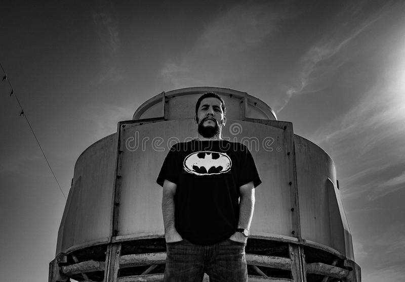Man in Batman Print Shirt Stand Against Container stock photography