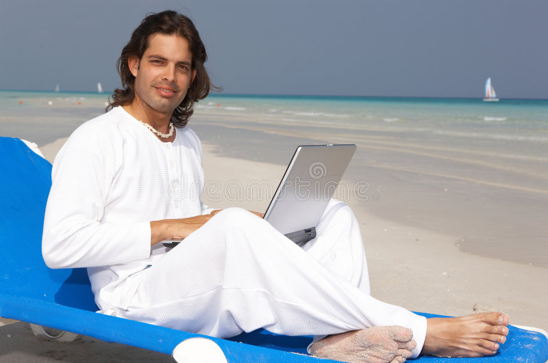 Man on the Beach. Young handsome Man on the beach using laptop royalty free stock photography