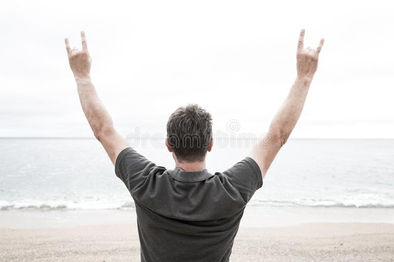 Man On Beach with Arms raised in Horns gesture. A rear view of a man standing on a deserted beach and facing the ocean with his arms raised high whilst gesturing stock images