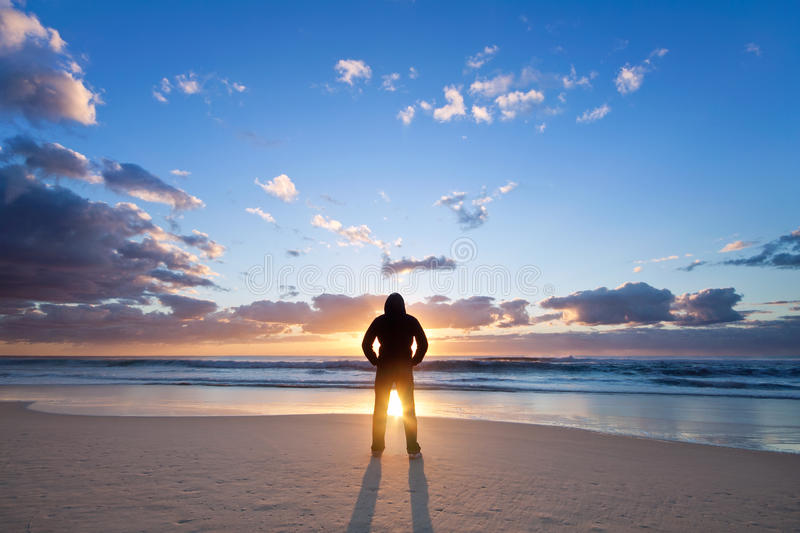Man on the beach in front of rising sun. With interesting cloud formation royalty free stock photo