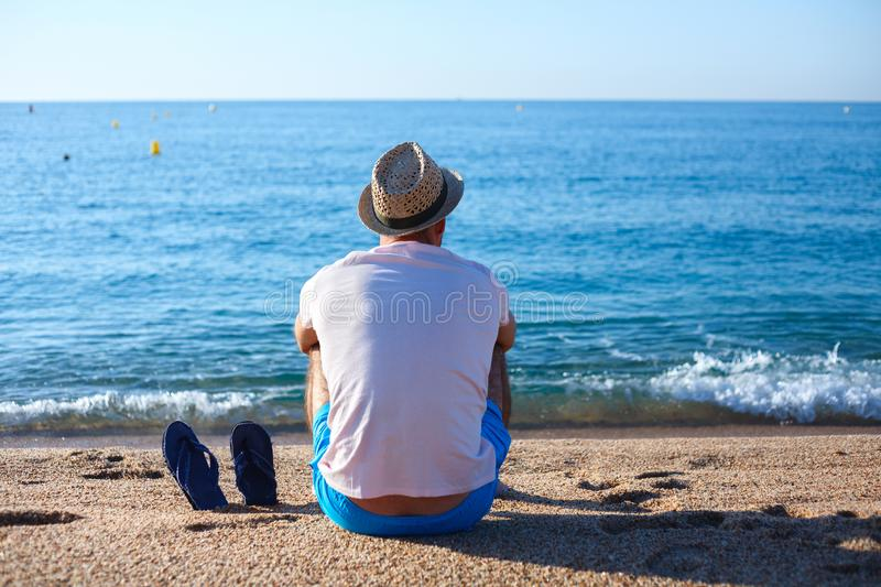 Man on beach, Lioret de Mar, Spain. Man sitting on beach wearing hat with flip flops in sand in Lioret de Mar, Spain stock photography
