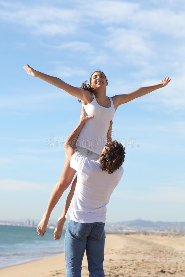 Download Man On The Beach Raising His Girlfriend Stock Image - Image: 29543965