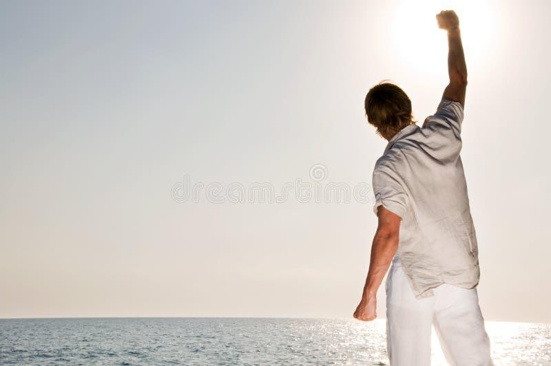 Man at the beach rising the hand royalty free stock photo