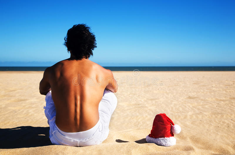 Man on the beach with santa hat. Young man on the beach with santa hat stock photos