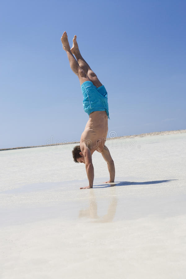 A man on a beach standing on his hands royalty free stock photo
