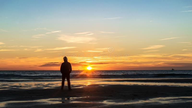Man on beach at sunset. Silhouette of man standing on beach at sunset stock photos