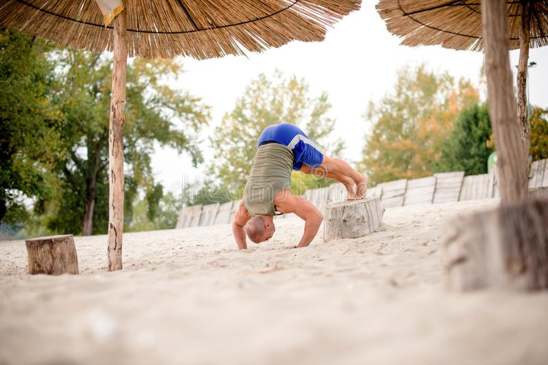 Man on beach trying headstand stock photo