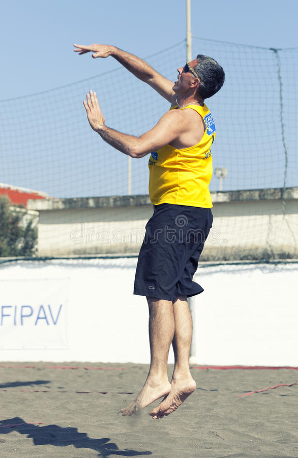 Man beach volleyball player serving ball jumping. April 12, 2015. Beach Volleyball Tournament men. Location: Ostia (Hibiscus), Rome. Italy. A man beach royalty free stock photography