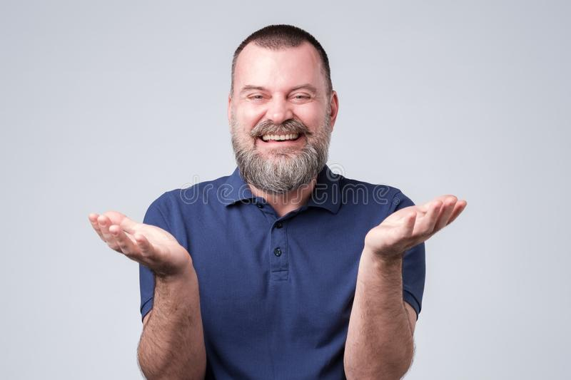 Man with beard in blue t-shirt laughing out loud, talking with friends, telling funny jok royalty free stock photography