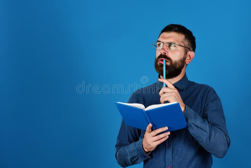 Man with beard and book. Idea and knowledge concept. Professor with thinking face. Teacher wears glasses and holds organizer. Textbook and pen in guys hands on royalty free stock photo