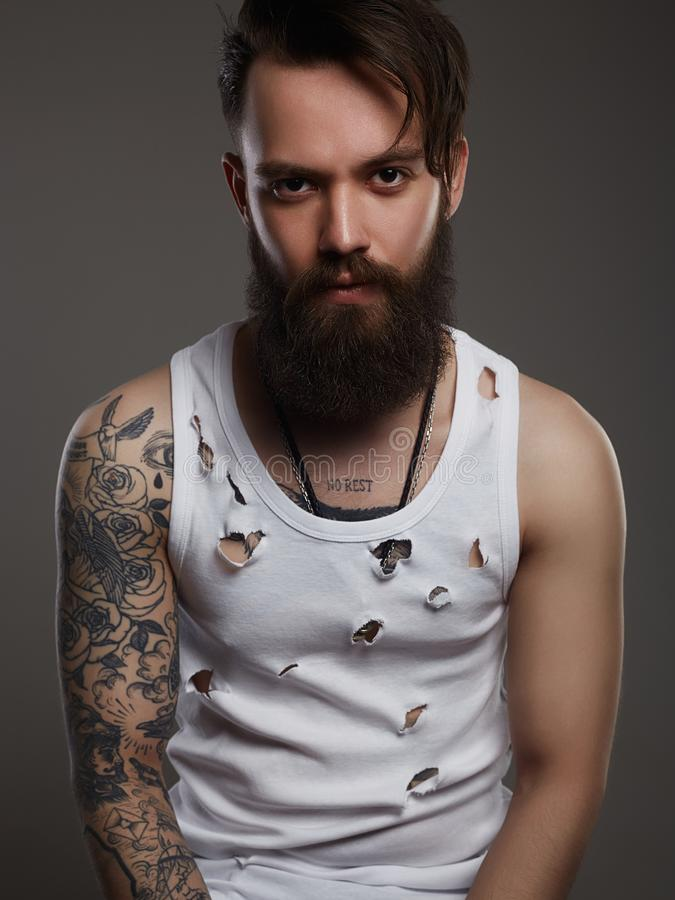 Man with beard. Boy with stylish haircut and tattoo. Handsome man with beard. Brutal bearded hipster in vintage torn dirty shirt. Boy with stylish haircut and stock image