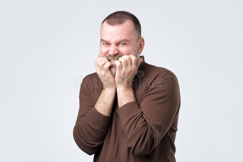 Man with beard in brown shirt biting nails in fear stock photography