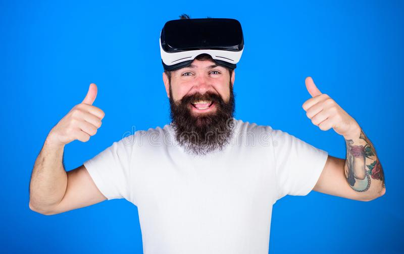 Man with beard and cheerful face enjoying virtual reality experience. Hipster with stylish beard and big smile happy stock image