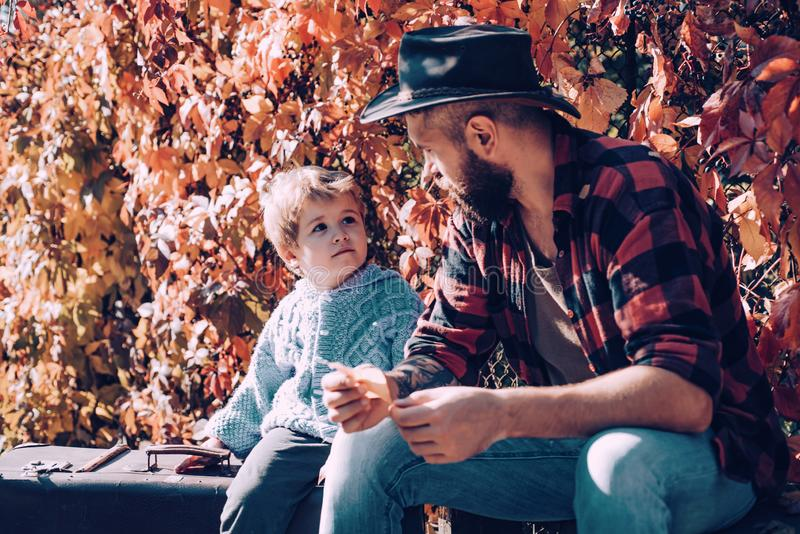 Man with beard, dad with young son in autumn park. Kid and his father are in autumn park. royalty free stock photo