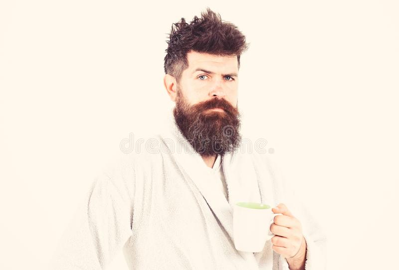 Man with beard and disheveled hair stands in bathrobe, holds mug with tea or coffee, white background. Morning rituals. Concept. Macho drowsy, sleepy with stock images