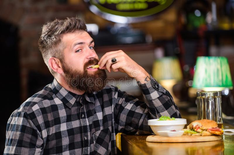 Man with beard drink beer eat burger menu. Enjoy meal in pub. Brutal hipster bearded man sit at bar counter. High. Calorie snack. Hipster relaxing at pub. Pub royalty free stock photography
