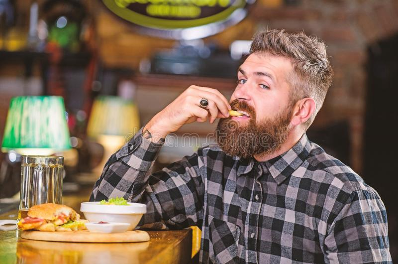 Man with beard drink beer eat burger menu. Enjoy meal in pub. Brutal hipster bearded man sit at bar counter. High. Calorie snack. Hipster relaxing at pub. Pub royalty free stock image