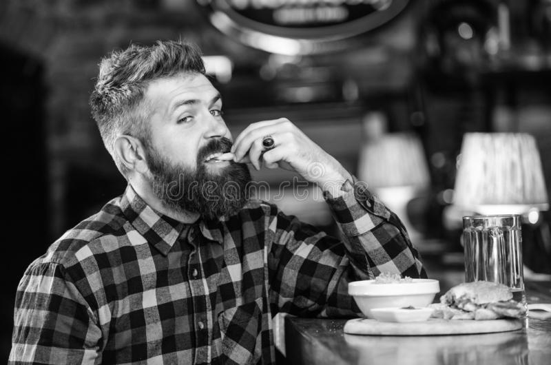 Man with beard drink beer eat burger menu. Enjoy meal in pub. Brutal hipster bearded man sit at bar counter. High. Calorie snack. Hipster relaxing at pub. Pub stock photography