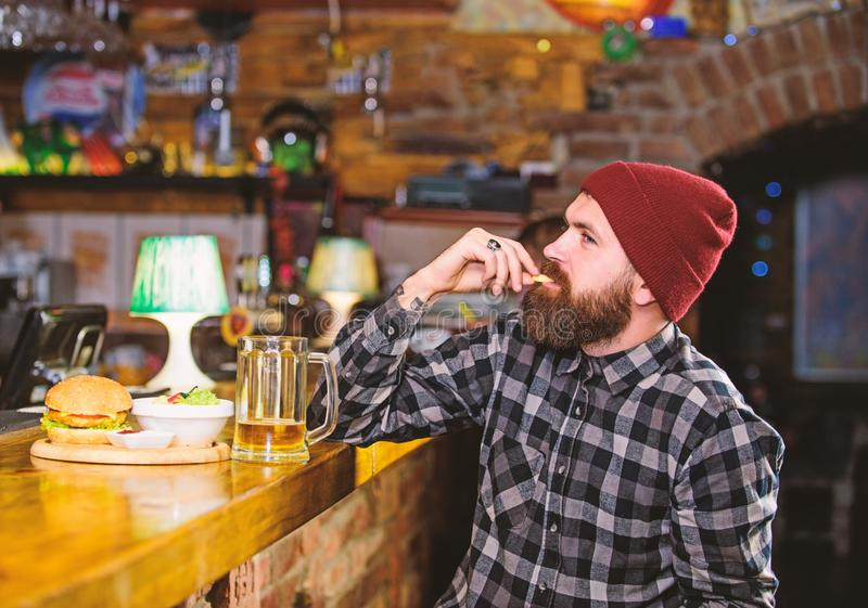Man with beard drink beer eat burger menu. Enjoy meal in pub. High calorie snack. Brutal hipster bearded man sit at bar. Counter. Hipster relaxing at pub. Pub stock photo