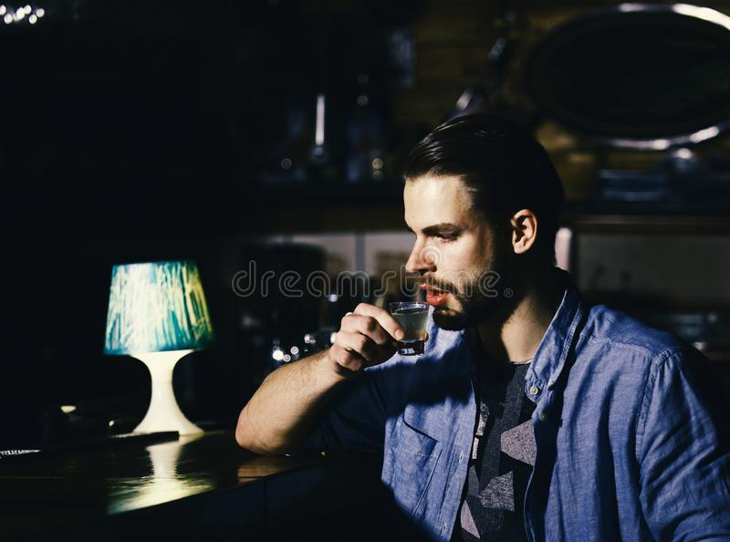 Man with beard drinks alcohol in bar on blurred background. royalty free stock photo