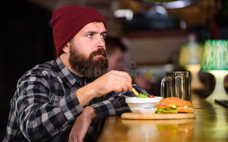 Man with beard eat burger menu. Brutal hipster bearded man sit at bar counter. Cheat meal. High calorie food. Delicious royalty free stock photo