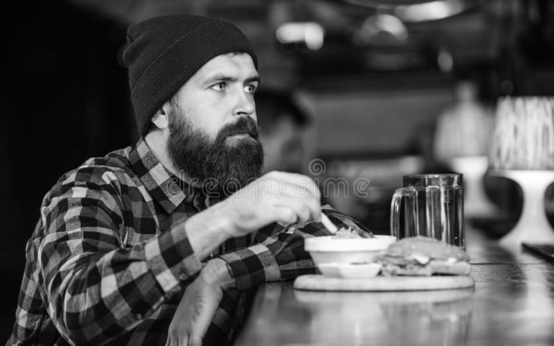 Man with beard eat burger menu. Brutal hipster bearded man sit at bar counter. Cheat meal. High calorie food. Delicious stock images