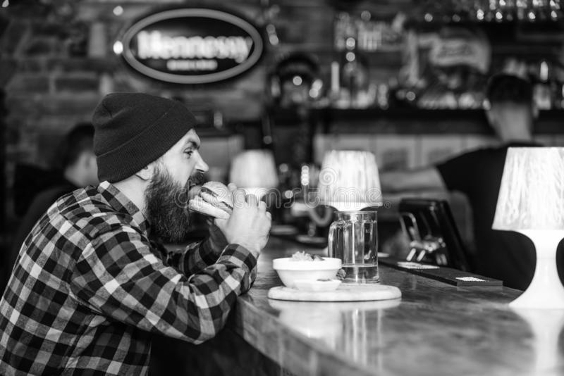 Man with beard eat burger menu. Brutal hipster bearded man sit at bar counter. High calorie food. Cheat meal. Delicious royalty free stock photos