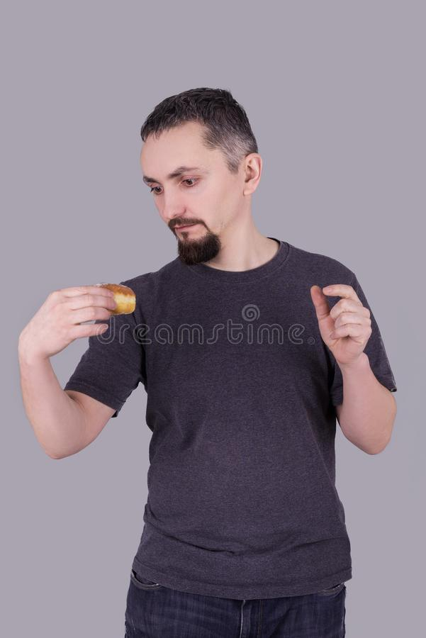 Man with a beard eating a bun over gray background stock photo