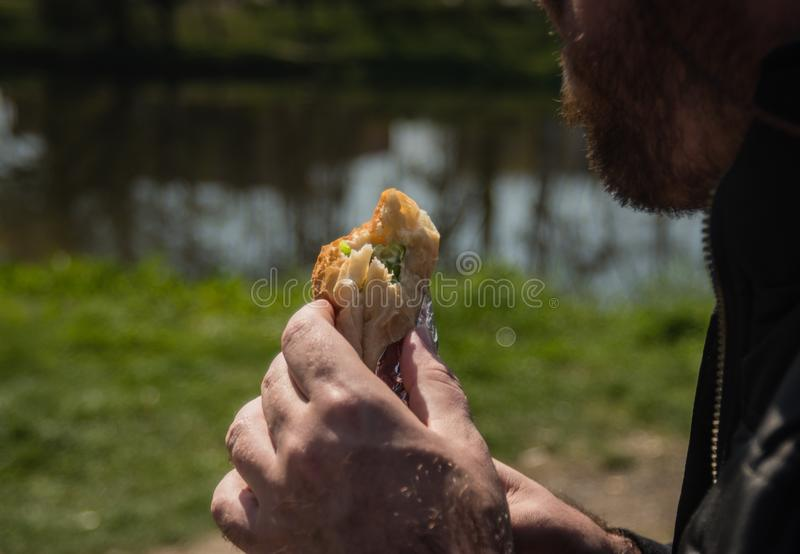 Man with beard eating fast food outside, closeup royalty free stock photos