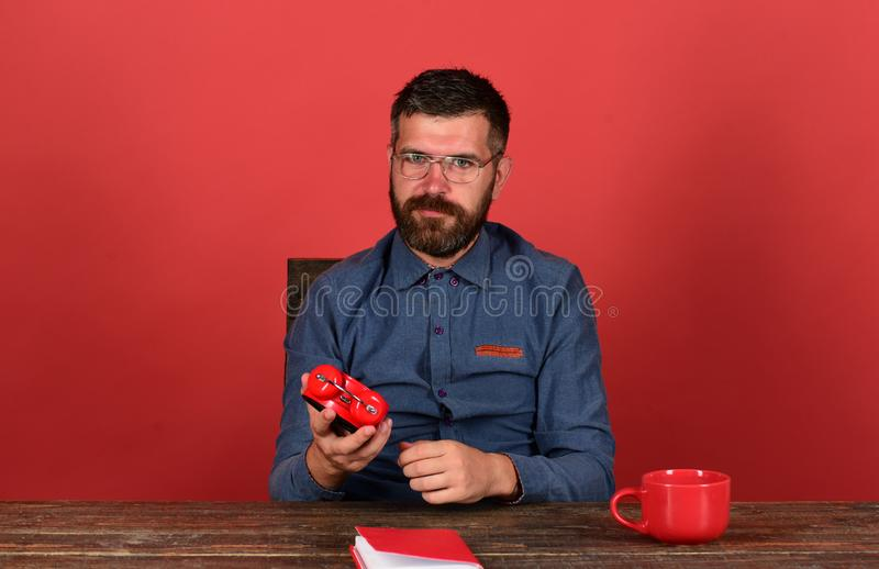 Man with beard and glasses holds alarm clock, red background royalty free stock image